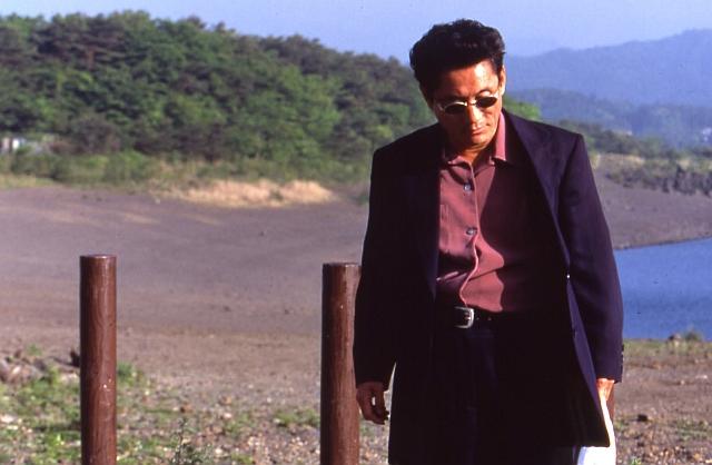 Takeshi Kitano as Yoshitaka Nishi going towards a man to beat him, 1996